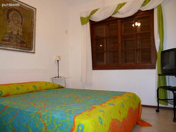 Tercer dormitorio, cama doble y vistas exteriores a jardín interno de la propiedad.