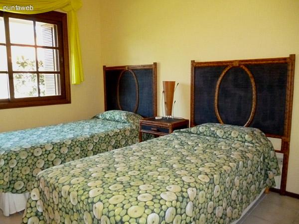 Cuarto dormitorio equipado con dos camas de una plaza, vistas exteriores a la calle y entorno.