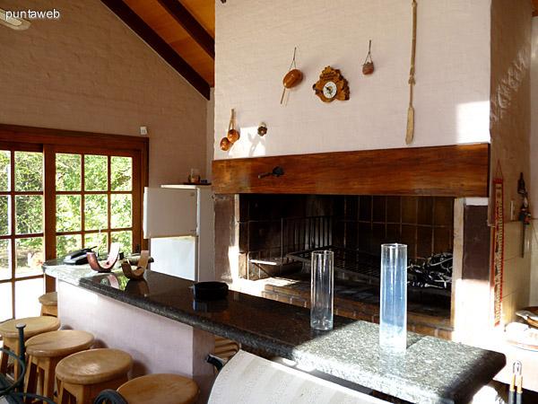 Parrillero amplio con electrodomésticos para su uso, mesa en madera con bancos.